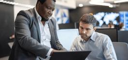 photo deux hommes qui discute devant un ordinateur